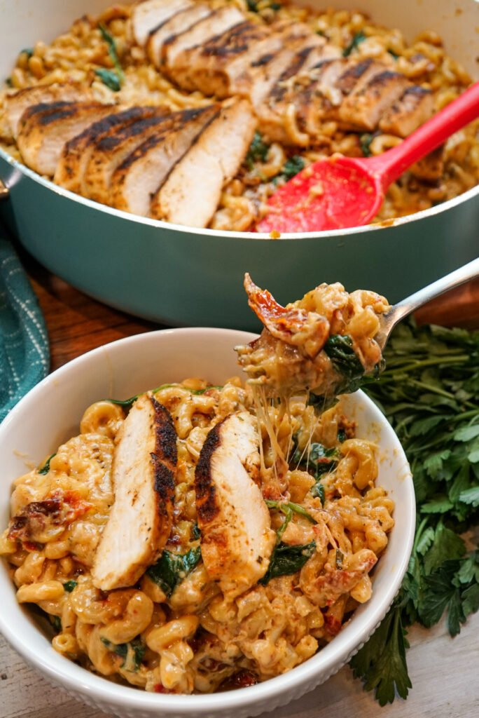 Tuscan chicken mac and cheese in a white bowl. Being picked up by a fork to show of the cheese, sun-dried tomatoes and spinach.