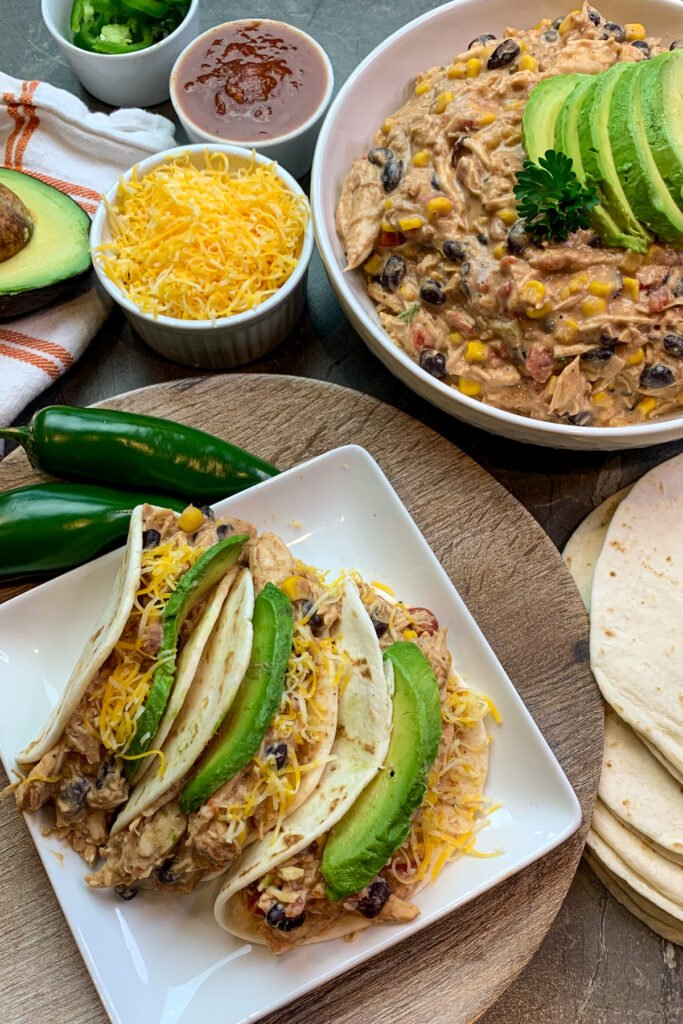 Slow cooker fiesta chicken in flour tortillas garnished with cheese and avocados.