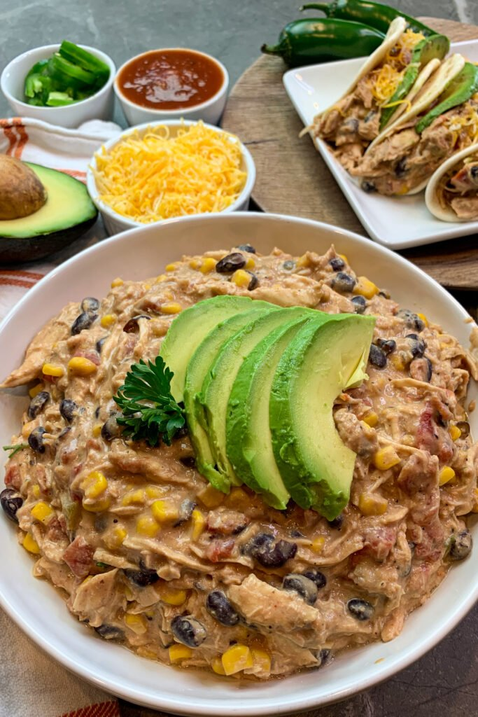 Close up of Crock Pot fiesta chicken in a white bowl and garnished with fresh avocado.