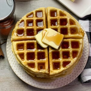 Close up of homemade waffles with two slabs of butter and syrup on them.