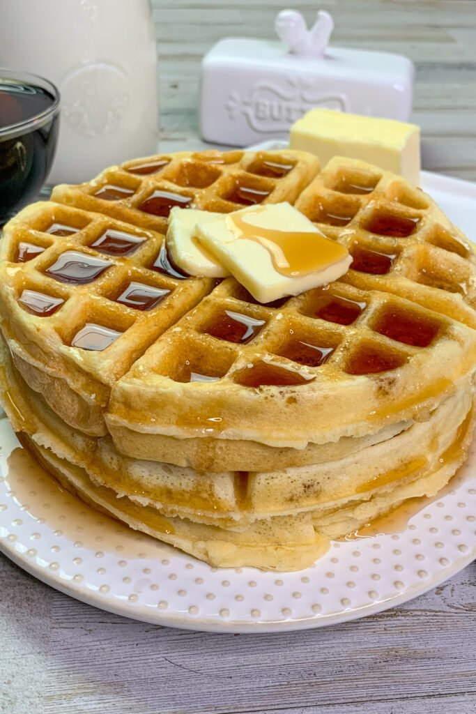 Fluffy waffles on a white plate covered in syrup.