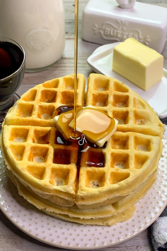 Close up of homemade waffles with syrup being poured on them.
