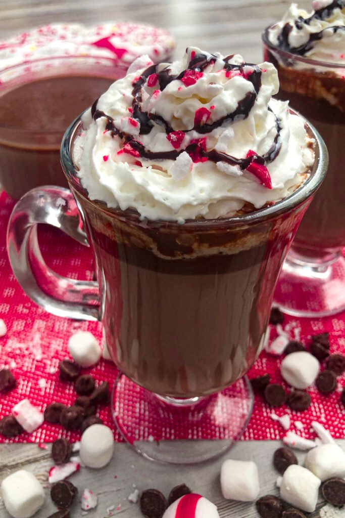 Peppermint hot chocolate served with whipped cream, chocolate drizzle, and chopped candy canes for garnish