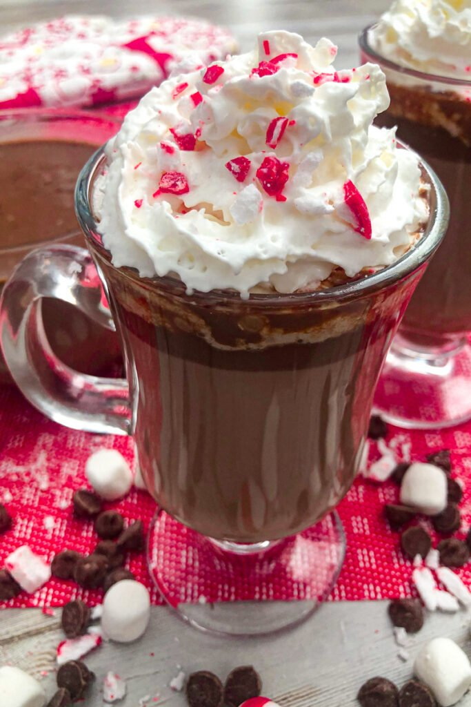 Peppermint hot chocolate served with whipped cream and chopped candy canes for a garnish